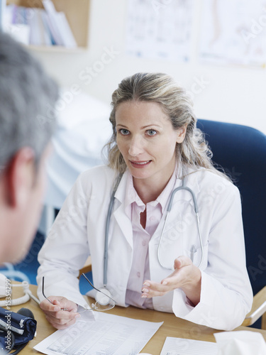 Female doctor at desk talking to man