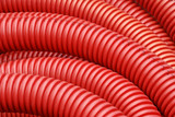 Coil of red plastic corrugated plumbing pipe in close up poster