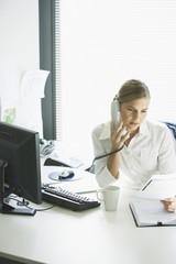 Businesswoman sitting at desk talking on telephone with document