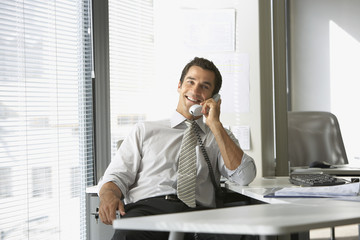 Businessman talking on telephone smiling