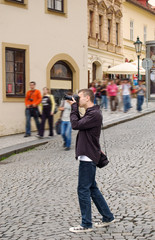 Photographer taking pictures outdoor and tourists passing by