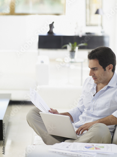 Man working on his laptop while relaxing at home