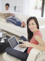 Woman working on her laptop while relaxing at home