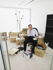 Male office worker talking on phone while sitting in a new office surrounded by boxes