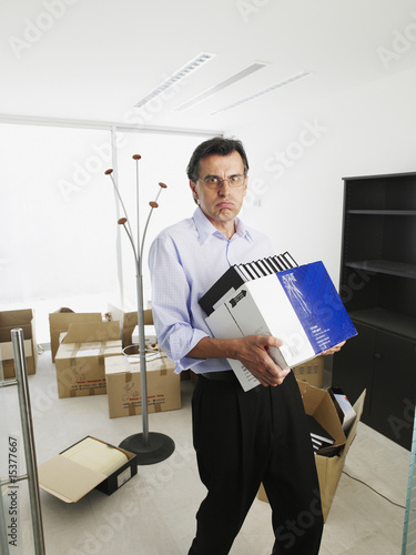 Male office worker carrying a box of binders and moving into a new office