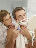 Young boy watching his father shaving in a mirror