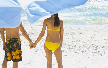 Man and woman holding hands at beach under umbrella