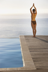 Woman on pool deck doing yoga
