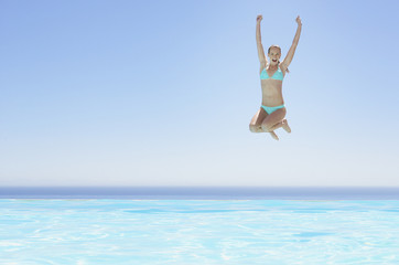 Woman leaping into infinity pool