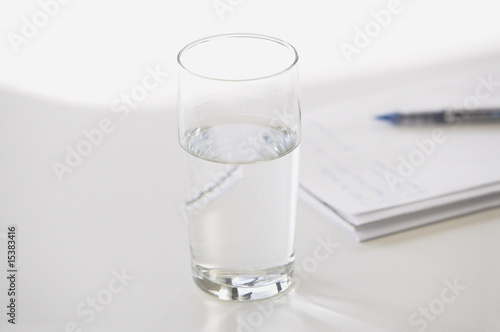 Closeup of glass of water with pen and notebook