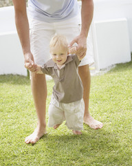 Man teaching son to walk