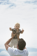 Man lifting baby outdoors