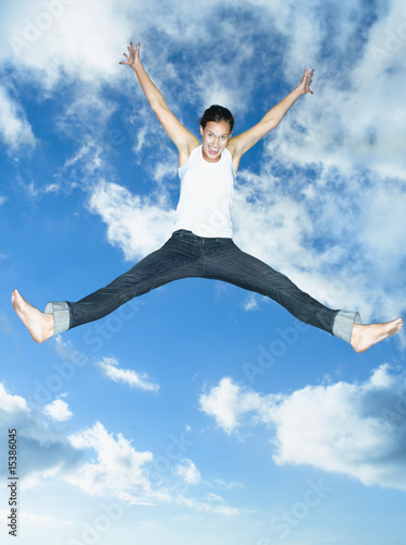 Woman leaping with blue sky and clouds
