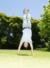 Boy doing handstand on grass with trees and blue sky