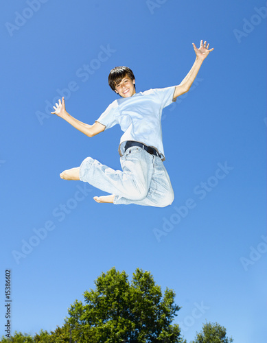 Boy leaping outdoors with blue sky and trees