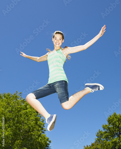Teenage girl leaping outdoors with blue sky and trees