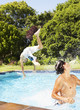 Two boys leaping and splashing in pool outdoors