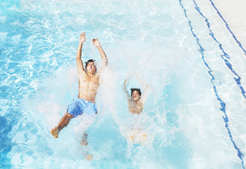 Two boys falling backwards into pool