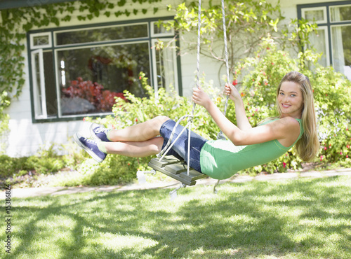 Teenage girl on swing outdoors in yard