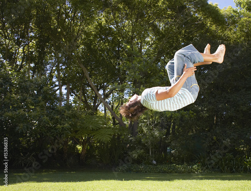 Teenage boy doing back flip outdoors with trees