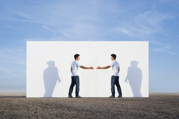 Man shaking hands with no one outdoors in front of wall