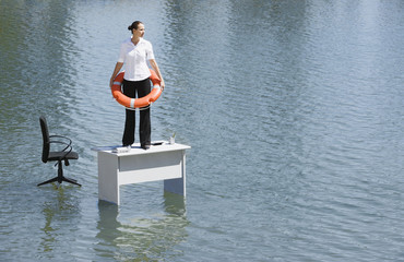 Businesswoman standing on desk with flotation device