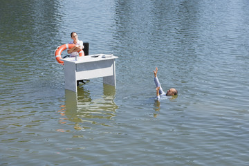 Businesswoman sitting at desk in water with flotation device and man drowning