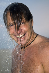Happy man under shower.