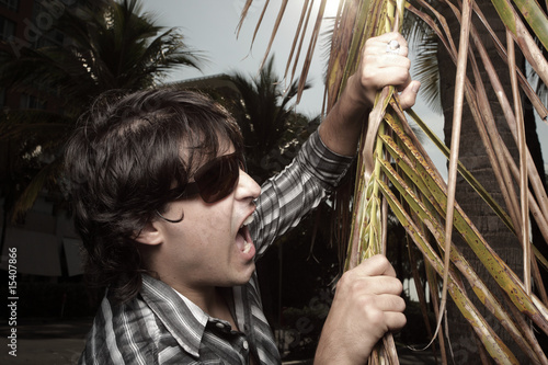 Man biting a palm frond