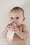 Baby girl drinks from a baby bottle by herself poster