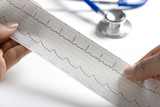 Hands holding a regular ECG with stethoscope on the background poster