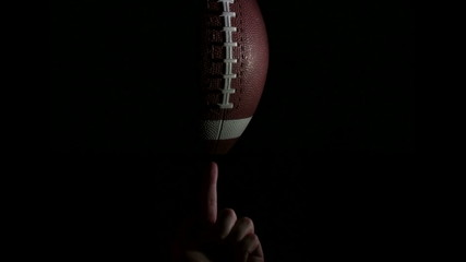 Football spins on finger against black - HD