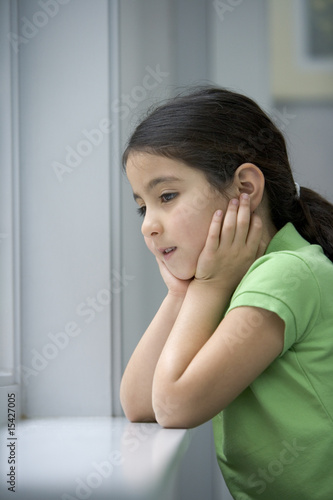 Sad little girl is looking out the window