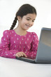 Little girl sitting behind a laptop