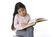 Little girl is studying a large book
