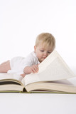 Little girl pretends to read a large book poster