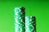 Stack of green casino chips against green background