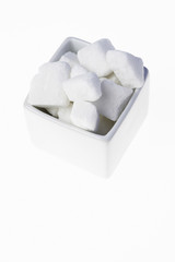 White granulated sugar cubes in a bowl isolated on white