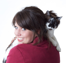 Young woman holding cat looking back over her shoulder