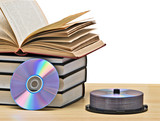 Pile of books  and DVD disk as symbols of old and new methods of poster