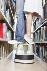 Waist down girl and boy standing on step stool in library