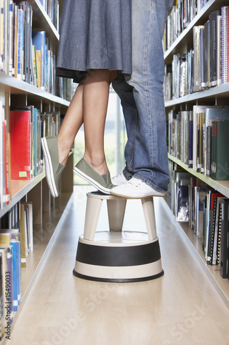 Waist down woman and boy standing on step stool in library