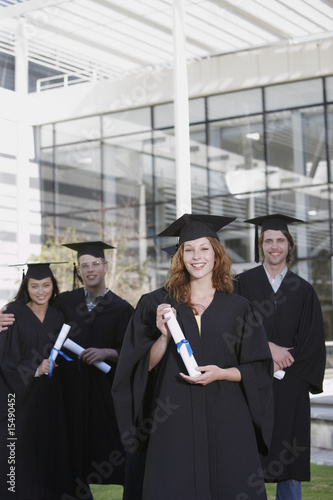 Young Adults in graduation gowns and mortar boards with diplomas