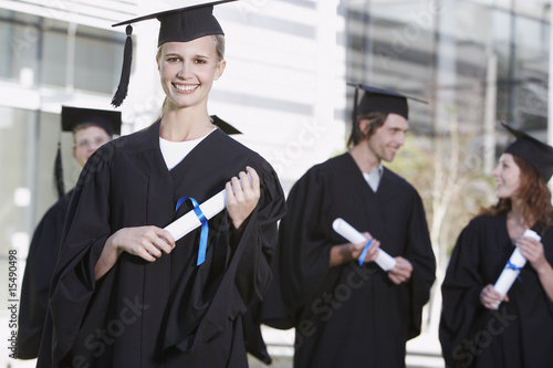 Teenagers in graduation gowns and mortar boards with diplomas