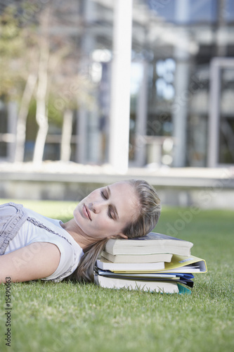 Teenage girl laying down in grass on books