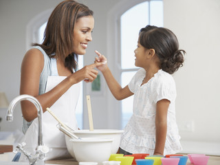 Mother and daughter baking cupcakes in kitchen