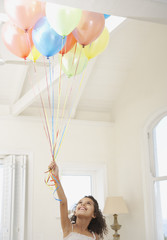 Girl with balloons looking up smiling
