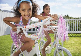 Two girls riding bicycles outdoors smiling