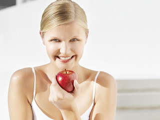 Woman with red apple outdoors