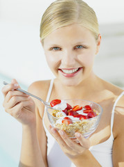Woman eating granola with yoghurt and strawberries